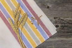 Granos y oídos del trigo en una tabla de madera Fotografía de archivo libre de regalías