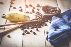 Granos y plátano de café de la historia de amor por la mañana en el backgr de madera Foto de archivo libre de regalías