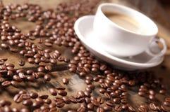 Granos y taza de café en atmósfera relajada, colores calientes y suavidad Fotografía de archivo