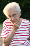 Granportrait 23. Portrait of senior citizen woman in deep thought, outdoors royalty free stock image
