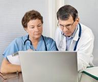 granska för sjuksköterska o för datordoktorsbärbar dator Royaltyfri Bild