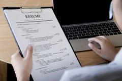 Granskning för affärsman hans meritförteckningapplikation på skrivbordet royaltyfri foto