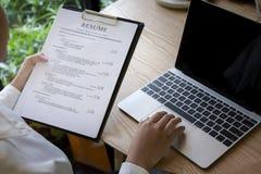 Granskning för affärsman hans meritförteckningapplikation på skrivbordet, bärbar datordator, jobbsökare royaltyfri bild