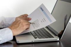 Granskning för jobbsökare hans meritförteckning på hans skrivbord med penna och dator l Royaltyfria Bilder