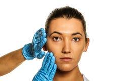 Granskning för plastikkirurgi. Arkivfoto