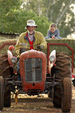 Grant-father Farmer. Grant-father and grant-daughter driving on tractor and wagon royalty free stock photography