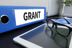 GRANT. Office folder on Desktop on table with Office Supplies. ipad Stock Photos