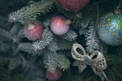 Granträdfilialer som dekoreras med bollar, och leksaken bugar Royaltyfri Foto