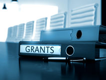 Grants on Office Folder. Toned Image. 3D. Folder with Inscription Grants on Wooden Working Table. Grants - Concept. Grants - Ring Binder on Black Desktop stock photography