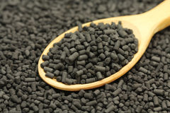 Granular carbon catalyst in a wooden spoon Royalty Free Stock Images