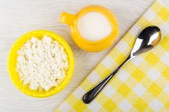 Granular cottage cheese in bowl, jug with yogurt, spoon, napkin Royalty Free Stock Photography
