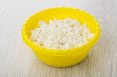 Granular fatless cottage cheese in yellow plastic bowl on table Royalty Free Stock Image