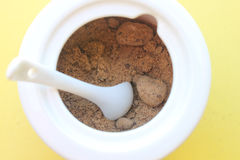 Granulated brown sugar. Cup of sugar is placed on a yellow background Stock Photos