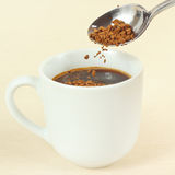 Granulated coffee is poured from spoon in a cup Royalty Free Stock Photos