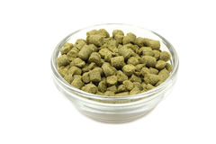 Granulated green hops in a glass bowl. On a white background Royalty Free Stock Images