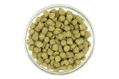 Granulated green hops in a glass cup. On a white background Royalty Free Stock Photos