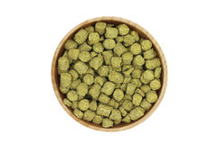 Granulated green hops in a wooden bowl. On a white background Stock Images