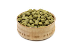 Granulated green hops in a wooden cup. On a white background Royalty Free Stock Photography
