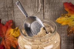 Granulated maple sugar in a jar of glass. Maple leaves in decoration and wooden planks in background Stock Images