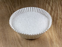 Granulated sugar in  paper muffin cup Royalty Free Stock Photos
