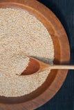 Granuli di legno della quinoa e del cucchiaio Fotografia Stock
