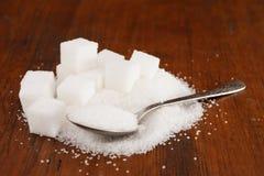 Granulierter raffinierter Zucker in einem Löffel mit einigen Würfeln auf einem braunen hölzernen Hintergrund Lizenzfreies Stockfoto