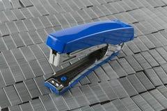 Grapadora azul en el montón de grapas Imágenes de archivo libres de regalías