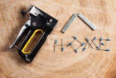 Grapadora de la construcción en fondo de madera foto de archivo libre de regalías