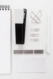 Grapadora negra con los clips y endecha del plano de las etiquetas engomadas Imagen de archivo libre de regalías