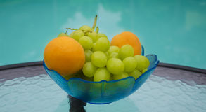 Grape and apricots by the swimmimg pool. Grape and apricots in glass plate on table by the swimming pool Royalty Free Stock Images