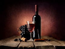 Grape in basket with wine. On a wooden table Royalty Free Stock Image