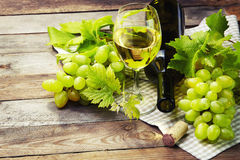 Grape, a bottles and glass of  white wine with grape on wooden t Stock Photo