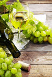 Grape, a bottles and glass of  white wine with grape on wooden t Royalty Free Stock Photo