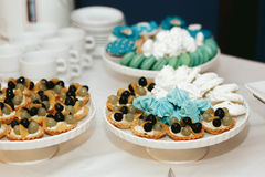 Grape-cheese baskets and blue sweets on the coffee table Royalty Free Stock Photo