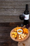 Grape, cheese, figs and honey with a bottle and glass of red win Royalty Free Stock Photo