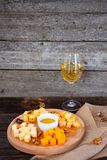 Grape, cheese, figs and honey with a glass of  white wine on woo Stock Photo