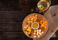 Grape, cheese, figs and honey with a glass of  white wine on woo Royalty Free Stock Photo