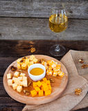 Grape, cheese, figs and honey with a glass of  white wine on woo Royalty Free Stock Images