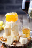 Grape, cheese, figs and honey with a glasses wine. Stock Photos