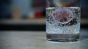 Grape floating in a glass with sparkling water stock video footage
