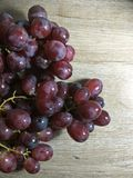 Grape on wooden table background. A grape is a fruit, botanically a berry, of the deciduous woody vines of the flowering plant genus Vitis. Grapes can be eaten royalty free stock images