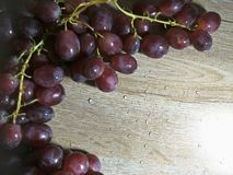 Grape on wooden table background. A grape is a fruit, botanically a berry, of the deciduous woody vines of the flowering plant genus Vitis. Grapes can be eaten stock images
