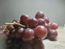 Grape on wooden table background. A grape is a fruit, botanically a berry, of the deciduous woody vines of the flowering plant genus Vitis. Grapes can be eaten stock image
