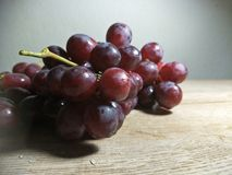 Grape on wooden table background. A grape is a fruit, botanically a berry, of the deciduous woody vines of the flowering plant genus Vitis. Grapes can be eaten royalty free stock photos