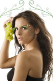 The grape and the girl. Portrait of a cute brunette with bodypaint on her face keeping green grape near Royalty Free Stock Photo