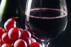 Grape and glass with red wine. On a black background Royalty Free Stock Photo