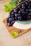Grape and Grapevine in Blue Bowl. On Brown Wooden Background stock images