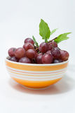 Grape with green leaf in orange bowl Stock Photos