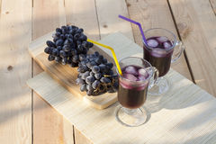 Grape juice cooler with ice in glass and glass of fresh blue grapes on a wooden table Royalty Free Stock Image