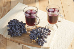 Grape juice cooler with ice in glass and glass of fresh blue grapes on a wooden table Stock Images
